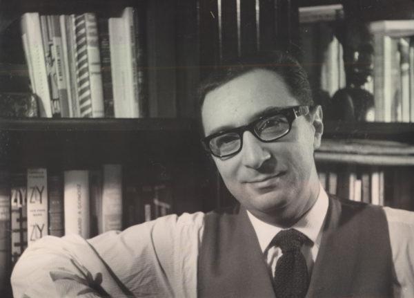 Uśmiechnięty mężczyzna pozuje na tle regału z książkami.