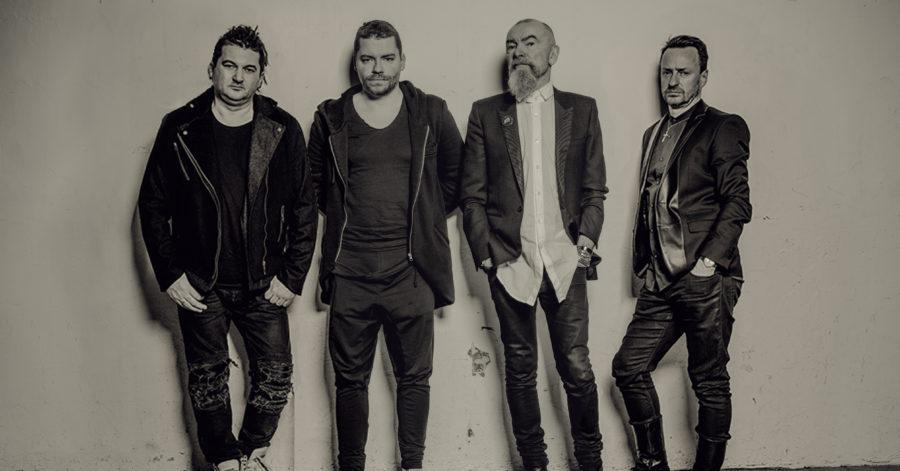 Czterech mężczyzn pozuje na tle białej ściany.