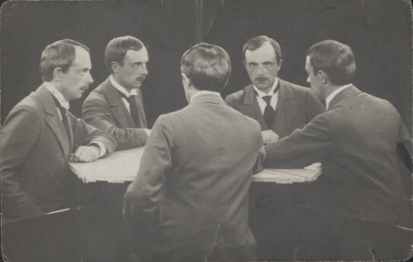 Pięciu identycznych mężczyzn, ustawionych w kierunku centrum, siedzi przy pięciokątnym stole.