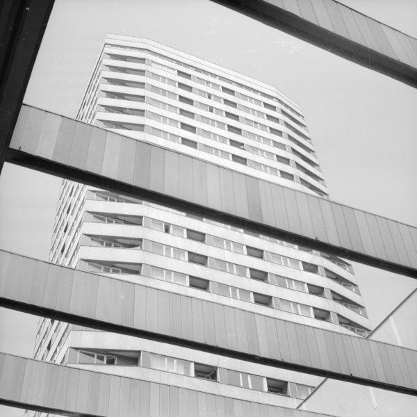 Czarnobiałe zdjęcie wieżowca z perspektywy człowieka na dole, patrzącego przez metalowe belki.