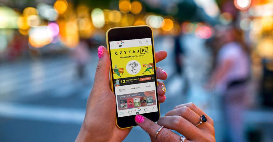 Na ekranie smartfonu, trzymanego w dłoniach, wyświetla się strona czytaj.pl