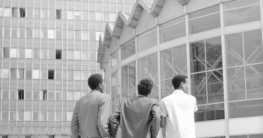 Trójka elegancko ubranych mężczyzn stojących przed Rotundą – przeszklonym budynkiem w kształcie walca.
