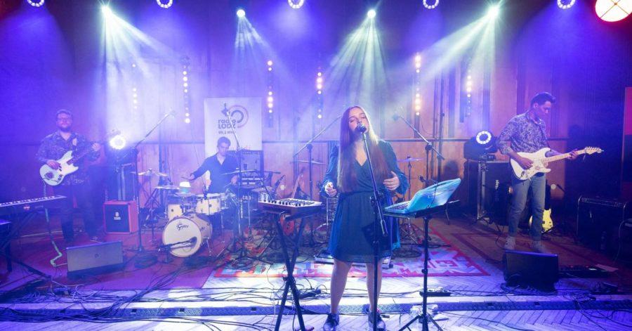Zespół muzyczny występuje na dobrze oświetlonej scenie.