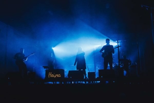 Zespół muzczny gra koncert. Dym na scenie i słabe światło sprawiają, że widać jedynie ciemne sylwetki członków zespołu.