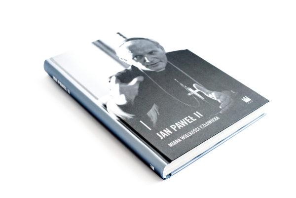 """Książka: """"Jan Paweł II - miara wielkości człowieka"""", z czarnobiałym portretem papieża na okładce."""