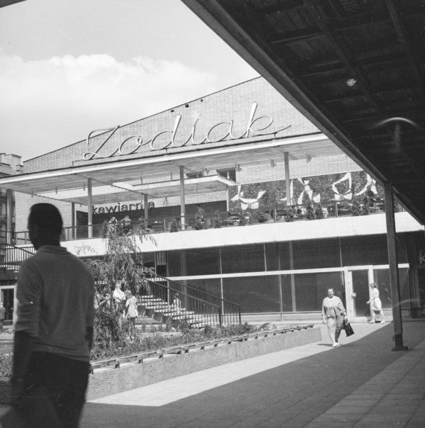 Odwrócony elegancki mężczyzna na tle fasady budynku kawiarni z neonem Zodiak na dachu