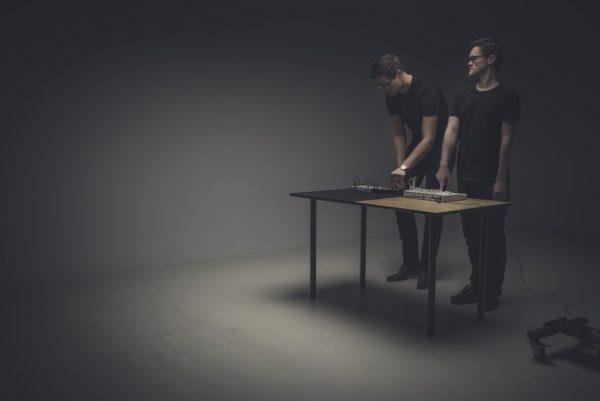Dwóch mężczyzn tworzy muzykę elektroniczną na mikserach, ustawionych na ławce, w kącie sali.