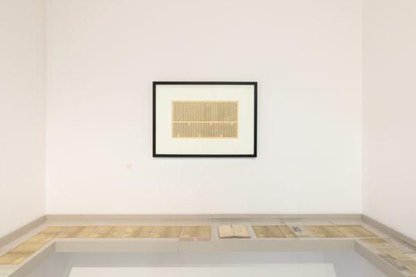 Żółta kartka papieru, która wygląda jak pożółkła strona z gazety, wisi w ramce na ścianie. Pod nią znajduje się gablota przymocowana do ścian bocznych i frontowej, w której znajdują się stare kartki papieru.