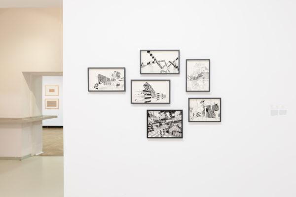 Na białej ścianie wiszą szkice abstrakcyjnych figur w ramkach.