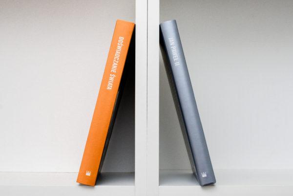 Dwie książki przechylone ku sobie oddzielone pionową ścianą regału. Po lewej książka z tytułem na grzbiecie: Doświadczenie Świata, po prawej - Jan Paweł II