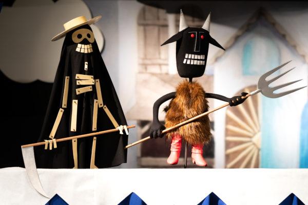 Dwie lalki na scenie, ustawione profilem. Lalka po lewej przedstawia śmierć, po prawej – diabła.
