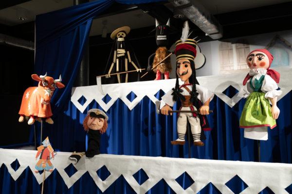 Dwie sceny teatru lalek, na bliższej pięć lalek przymocowanych prętami, na dalszej scenie dwie lalki przymocowane prętami.