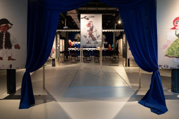 Wejście na wystawę, brama stworzona z odsłoniętej kurtyny, za którą znajdują się eksponaty.
