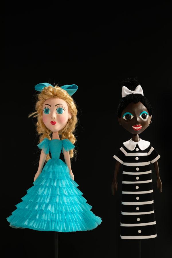 Dwie lalki ustawione frontem, przymocowane prętem do podłogi. Po lewej lalka wygląda jak księżniczka, po prawej lalka w stroju służki.
