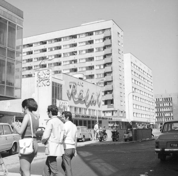 Trójka ludzi przechodzących przez ulicę w centrum miasta, na tle budynku z neonem Kino Relax