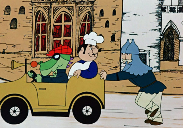 Dwóch strażników pcha samochód, w którym na fotelu pasażera siedzi kucharz, a prowadzi go smok w ubraniu.