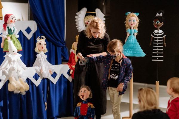 Kobieta na scenie uczy kilkuletnią dziewczynkę jak poruszać marionetką.