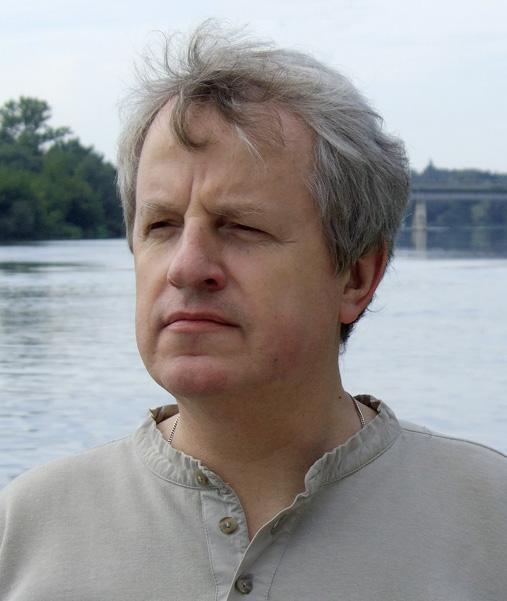 Mężczyzna pozuje do zdjęcia profilem na tle jeziora.