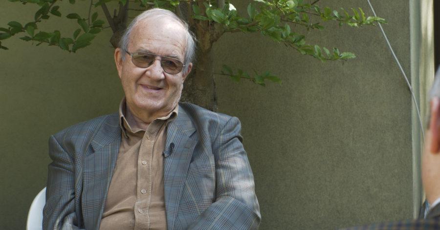 Starszy elegancko ubrany mężczyzna udziela wywiadu w ogrodzie.