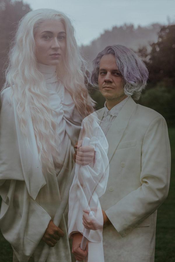 Kobieta stoi przed mężczyzną, jest delikatnie przezroczysta, dlatego widać przez nią fragment mężczyzny, który powinna zasłaniać. Para jest ubrana na biało, pozuje na polanie na tle lasu.