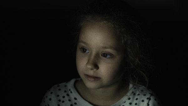 Zamyślona dziewczynka, ustawiona profilem, patrzy się przed siebie. W tle znajduje się ciemny materiał.