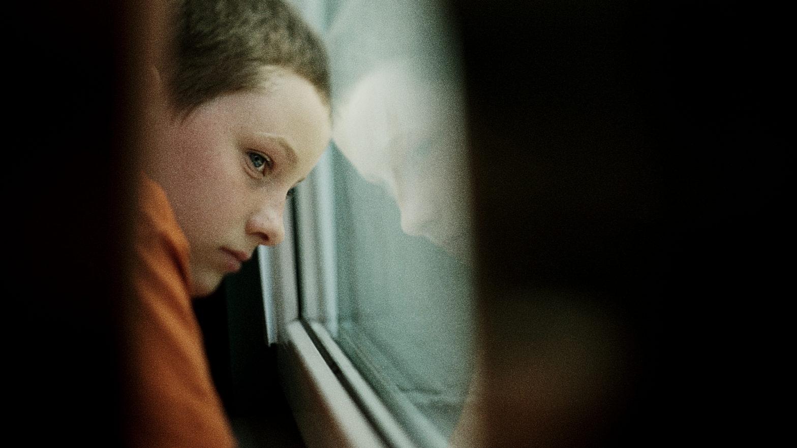Chłopczyk nostalgicznie patrzy przez okno. W szybie odbija się jego twarz.