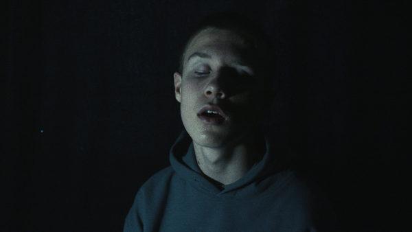 Chłopiec znajduje się na ciemnym tle, ma otwarte usta i zamknięte oczy.
