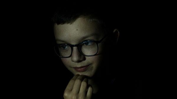 Chłopczyk w okularach nad czymś się zastanawia, drapie się ręką po brodzie. Postać znajduje się na ciemnym tle.
