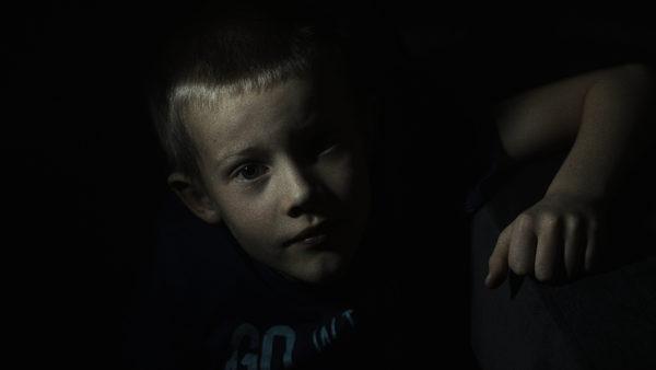Częściowo oświetlony chłopczyk patrzy się w obiektyw, swoją prawą rękę opiera na szarym prostokątnym kształcie. Tło jest ciemne.
