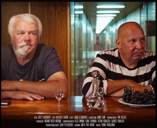 Dwóch mężczyzn w średnim wieku siedzi przy stole zastawionym wódką i winogronami. Mężczyźni patrzą się z uwagą na coś, znajdującego się poza kadrem. Za nimi znajdują się szklane drzwi, przez które widać długi, wąski korytarz.