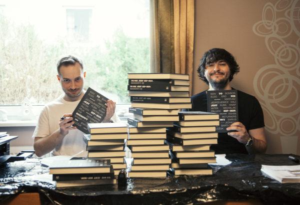 """Dwóch mężczyzn siedzi przy stole i pozuje z książką """"To nie jest hip-hop. Rozmowy"""". Na stole znajduje się sterta tych książek."""