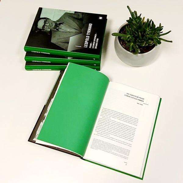 Kolaż kolorystyczny, po lewej stronie leżą książki ułożone w wachlarz, pod nimi otwarta książka, której lewa strona jest pusta i zielona, a prawa biała, zapisana czarnymi literami. Kompozycję dopełnia zielona roślina w białej doniczce, wypełnionej ciemną ziemią.