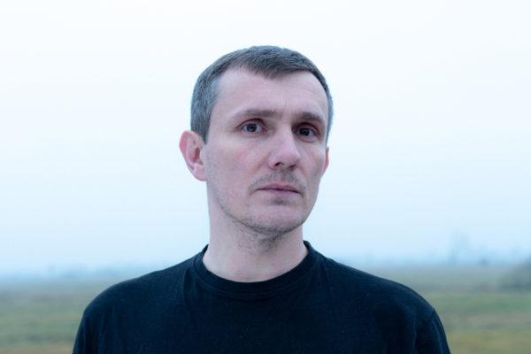 Portret mężczyzny w średnim wieku, który pozuje na tle zamglonego pola.