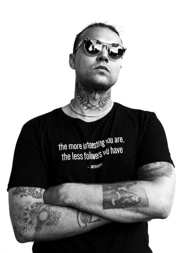 Mężczyzna pozuje dumnie, ręce ma skrzyżowane na piersiach. Twarz lekko odchyloną do tyłu, nosi okulary przeciwsłoneczne.