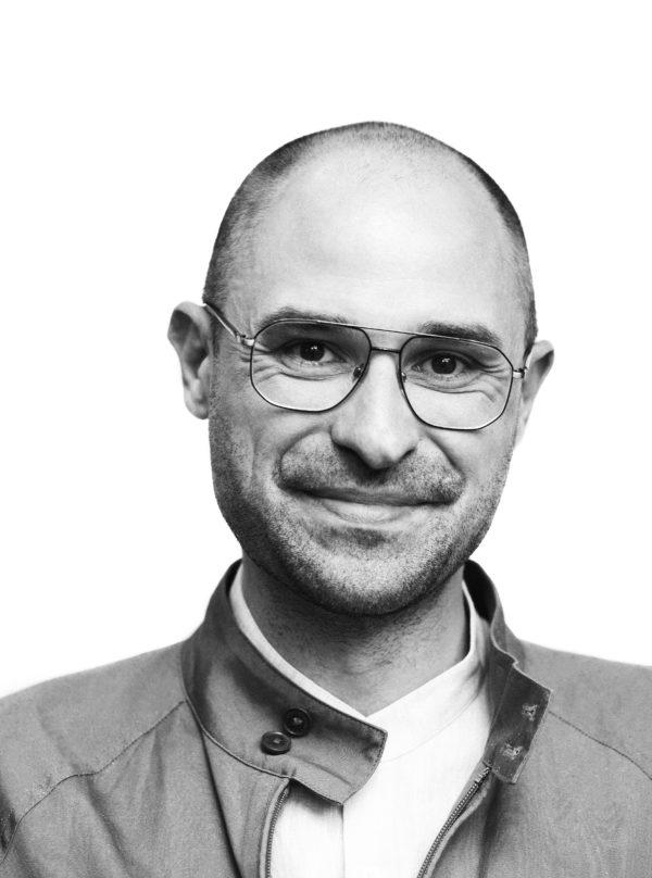 Uśmiechnięty mężczyzna, który ma owalną twarz. Nosi okulary korekcyjne, ma bardzo krótkie zarost i włosy.