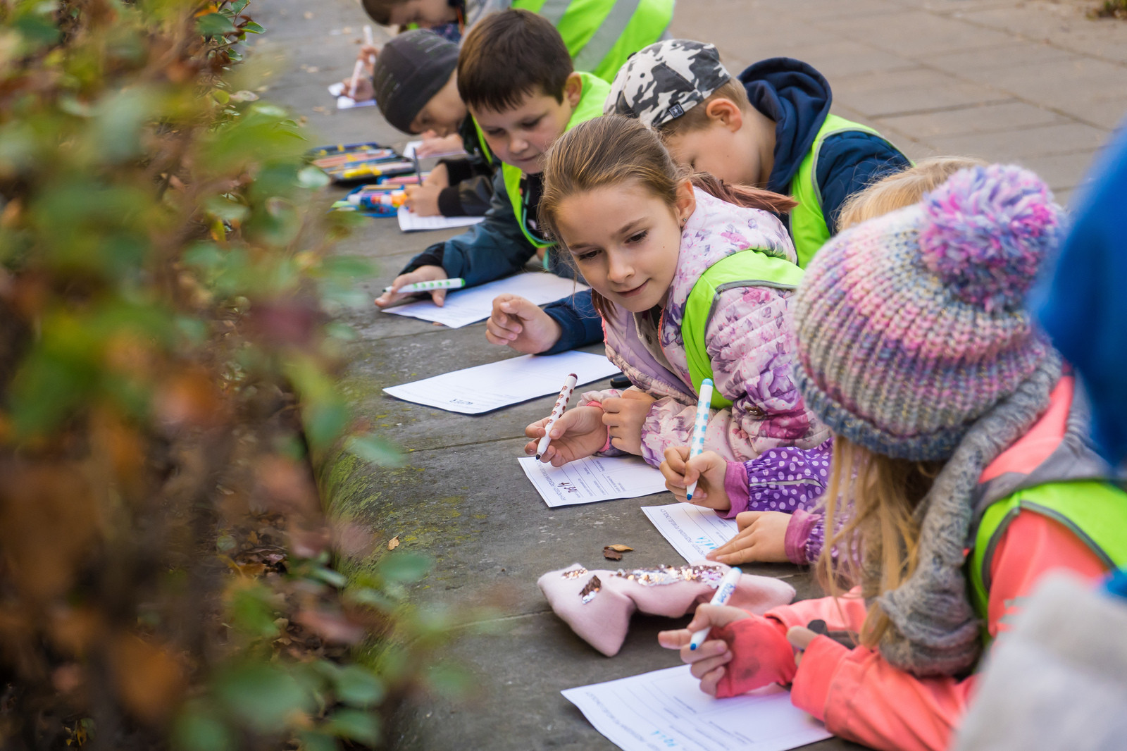 Grupa dzieci oparta o kamienny murek, zapisuje coś na kartkach..