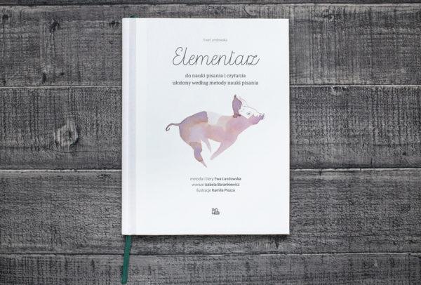 Okładka elementarza, na której znajduje się namalowana, biegnąca świnia.