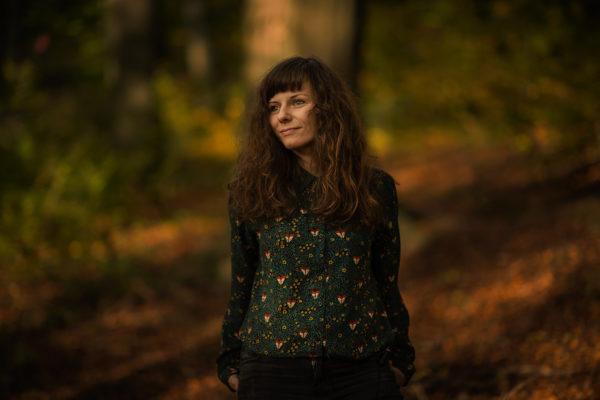 Młoda kobieta pozuje do zdjęcia. W tle znajduje się rozmyty las.