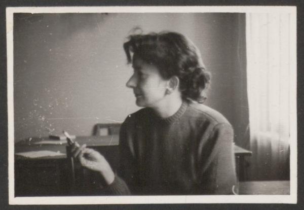 Młoda Wiesława Szymborska siedzi obrócona profilem. W ręce trzyma papierosa.