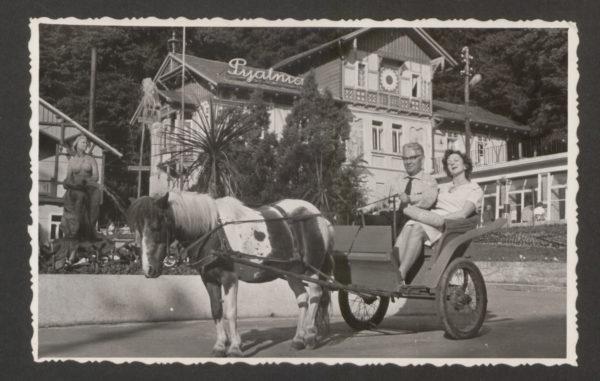 Wiesława Szymborska siedzi w powozie, trzyma pod rękę mężczyznę, który ma w rękach lejce. Niewielki powóz jest ciągnięty przez niewielkiego konia.