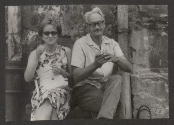 Wiesława Szymborska siedzi na ławce obok starszego mężczyzny, który pali papierosa.