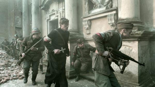 Polscy żołnierze uzbrojeni w karabiny i ksiądz z krzyżem w dłonie, przemykają po zniszczonym mieście.