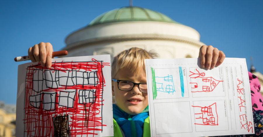 Dziecko pokazuje swoje kolorowe rysunki budynków.