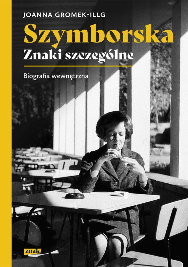 """Okładka książki pod tytułem: """"Wiesława Szymborska, Znaki szczególne"""", przedstawia bohaterkę biografii, która siedzi przy stoliku w pustej kawiarni i pali papierosa."""