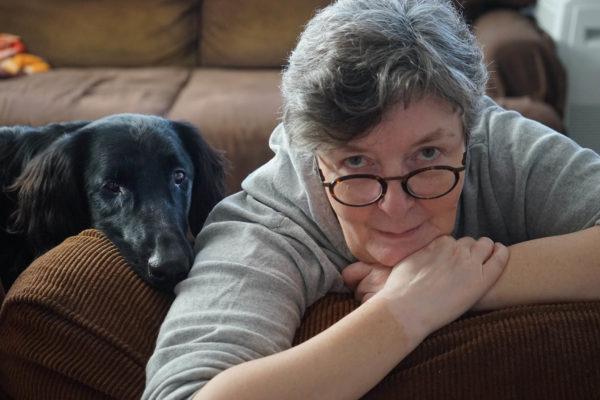 Starsza kobieta siedzi oparta o krawędź kanapy, obok niej siedzi pies w podobnej pozycji.