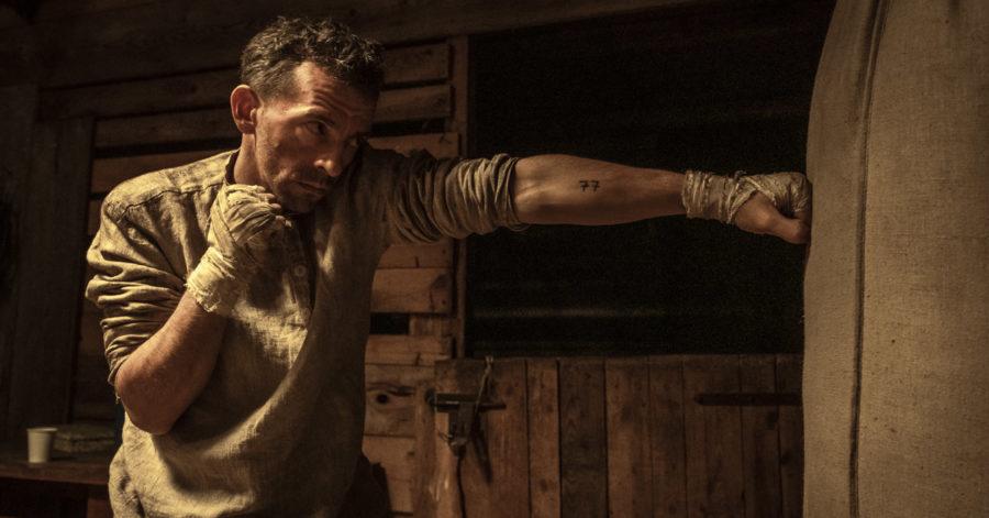 Mężczyzna w zniszczonych ubraniach uderza w worek bokserski w drewnianym baraku.