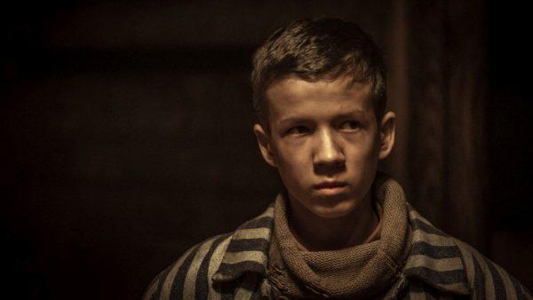 Kadr z filmu, chłopiec w ubraniu więziennym patrzy się poważnie na coś nieujętego w kadrze.
