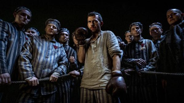 Kadr z filmu, w rogu ringu stoi bokser gotowy do walki. Za nim stoją więźniowie, którzy oglądają walkę.