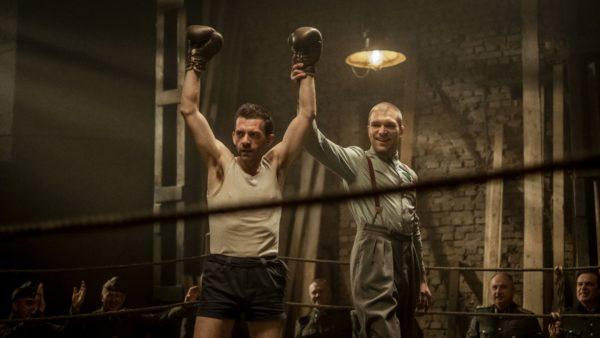 Kadr z filmu, sędzia unosi rękę boksera na ringu, ukazuje w ten sposób zwycięzcę walki. Bokser ma uniesione obie ręce do góry w geście zwycięstwa.