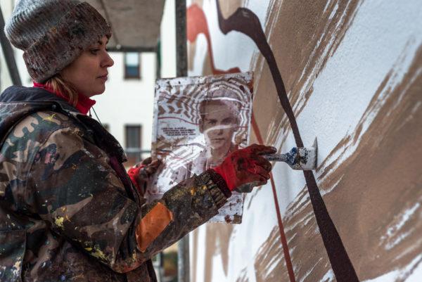 Kobieta na rusztowaniu, w jednej ręce trzyma projekt muralu, drugą ręką maluje.